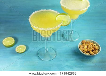 Lemon Margarita cocktails with wedges of lime and a salted nuts snack, on a vibrant turquoise background with copy space