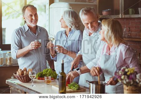 Nice traditions. Positive aged smiling frineds resting together and expressing gladness while cooking in te kitchen