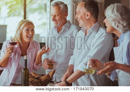 Crack a joke. Positive delighted aged couples standing in the kitchen and talking while cooking tatsy dinner