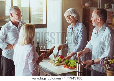 Cook with love. Cheerful aged smiling couples standing in the kitchen and cooking festive dinner while expressing positivity