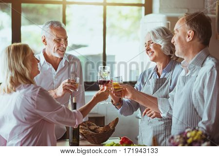 Cheers. Positive aged smiling couples standing in the kitchen and drinking beveraged while enjoying celebration