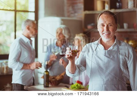 One more toast. Cheerful aged man smiling and standing in the kitchen while is friends enjoying celebration in the background