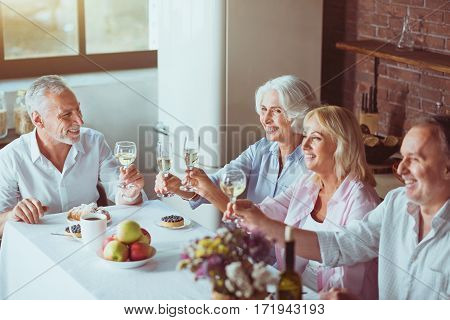 Best wishes. Cheerful smiling aged frineds sitting at the table and making toast while enjoying celebration