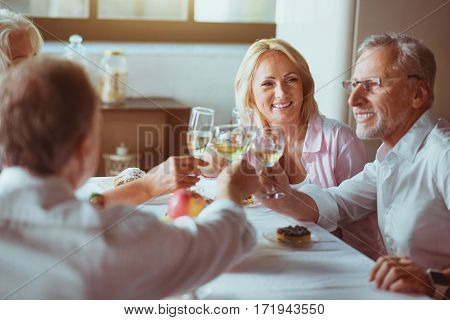 Pleasant talks. Positive delighted aged couples sitting at the table and drinking champagne while enjoying celebration
