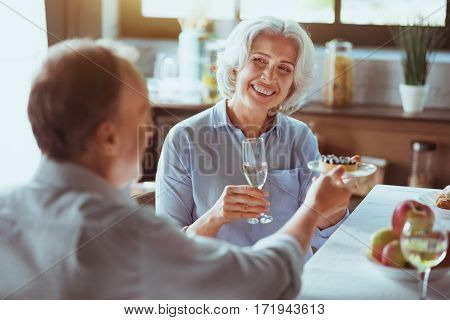 Thank you. Positive aged smiling couple enjoying festive dinner and drinking champagne while sitting at the table