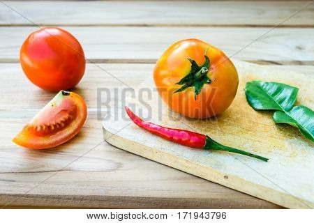 Tomatoes on chopping board with wooden table