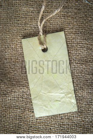 Light neutral beige Linen Fabric Background and blank blue Price Tag on natural hempen cord