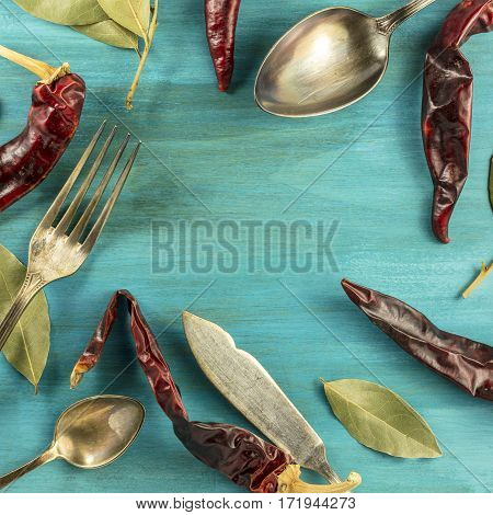 A square photo of vintage forks, spoons and knife on a vibrant turquoise background texture, forming a frame with chili peppers and bay leaves. Restaurant menu or special offer banner design template