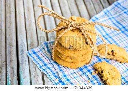 Tasty cookies with chocolate chops against wooden table