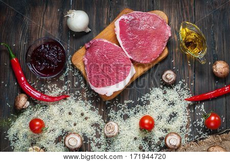 Ingredients for cooking healthy meat dinner. Raw uncooked beef rib eye steaks with mushrooms rice herbs and spices on table background.