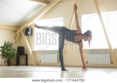 Young attractive happy woman practicing yoga, standing in Ardha Chandrasana exercise, Half Moon pose, working out wearing sportswear, grey tank top, pants, indoor full length, home interior background