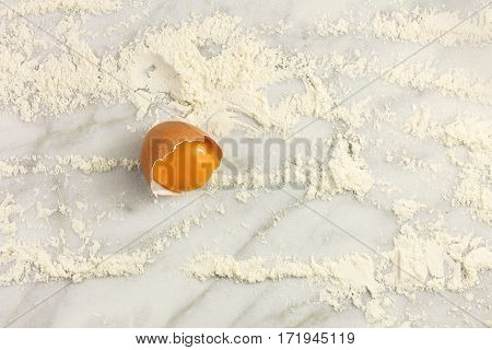 An overhead photo of an egg on a white marble table covered with flour. Cooking background with plenty of copy space