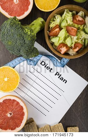 Food And Sheet Of Paper With A Diet Plan On A Dark Wooden Table.