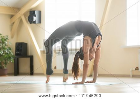Young cool attractive woman practicing yoga, standing in Urdhva Dhanurasana exercise, Bridge pose, working out, wearing grey sportswear, indoor full length, home or sport club interior background