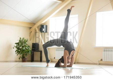 Attractive woman practicing yoga, doing variation of Elbow Bridge exercise, Dvi Pada Viparita Dandasana pose, working out wearing grey sportswear, indoor full length, home or club interior background
