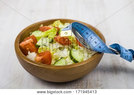 Salad In Wooden Bowl, Fork And Measuring Tape On A Table Close-up.