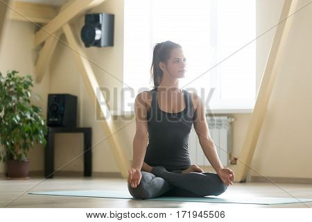 Young attractive woman practicing yoga, sitting in Padmasana exercise, Lotus pose, working out, wearing sportswear, grey tank top, pants, indoor full length, home interior background