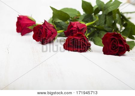 Red Roses On A Wooden Background.
