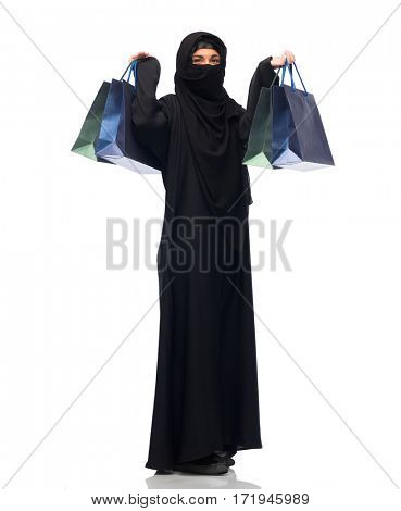 sale, consumerism and people concept - muslim woman in hijab with shopping bags over white background