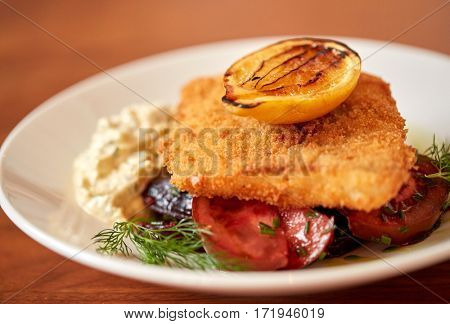 food, new nordic cuisine, culinary and cooking concept  - close up of breaded fish fillet with tartar sauce and oven-baked beetroot tomato salad on plate