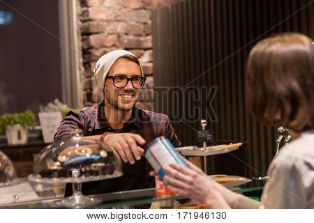 small business, people and service concept - happy man or waiter serving female customer at vegan cafe
