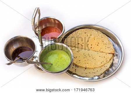 Indian bread served with the traditional assortment of sauces, in the typical tableware, on a white background. Selective focus