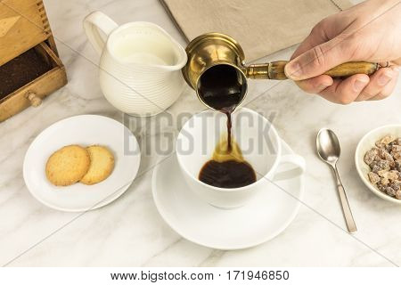 Coffee poured into a cup from a coffee pot, with a milk jar and cane sugar. Selective focus