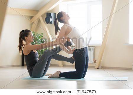 Young beautiful lady beginning yoga practice with private teacher at home, class, working out with professional female yogi instructor. Yoga trainer helps student to do Ustrasana exercise, Camel pose