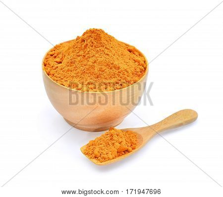turmeric powder in wooden bowl and spoon isolated on white background