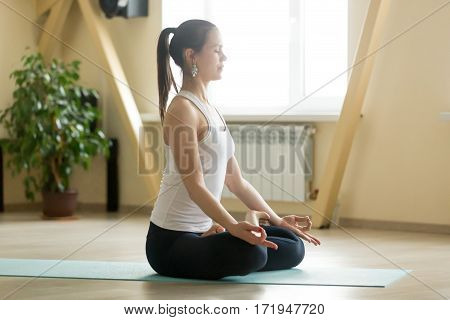 Young attractive woman practicing yoga, sitting in Padmasana exercise, Lotus pose with mudra, working out, wearing sportswear, white tank top, black pants, indoor full length, home interior
