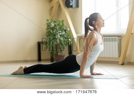 Young attractive woman practicing yoga, stretching in upward facing dog exercise, Urdhva mukha shvanasana pose, working out, wearing sportswear, white tank top, black pants, indoor full length, home