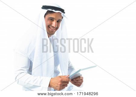studio shot of young man wearing traditional arabic clothing using digital tablet