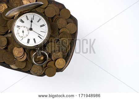 Time is money a bunch of coins with a pocket watch on top isolated on white