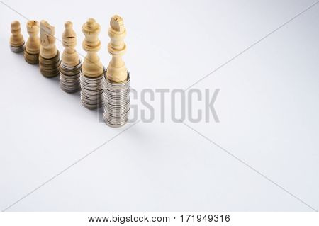 Growing coins stacks on white background. White chess figures standing on coins meaning power and career growth. Financial growth saving money business finance wealth and success concept.