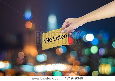 Hand Holding A We Listen Sign Made On Sugar Paper With City Light Bokeh As Background