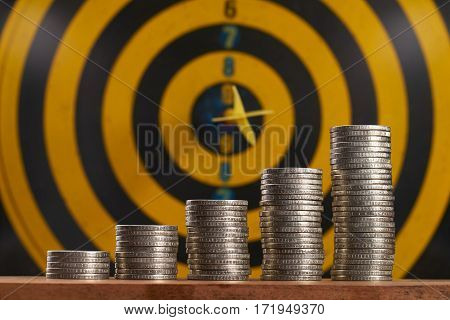 Yellow dart hit in the center of a target with stack of coins on white background with copy space. A idea about money / currency investment that must decide or think carefully