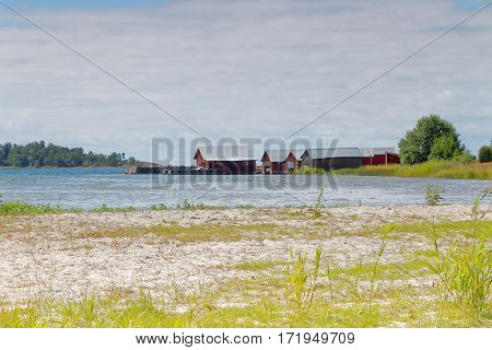 Distant red boathouses and a sand beach in the foreground in the archipelago in Aaland Finland