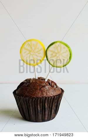 Birthday chocolate muffin with citrus lemon lollipops on white background