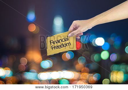 Hand Holding A Financial Freedom Sign Made On Sugar Paper With City Light Bokeh As Background