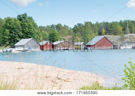 Red and gray boathouses rock and trees in the archipelago in Aaland Finland