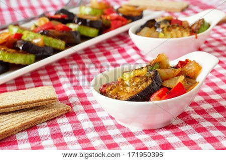 Grilled eggplant and zucchini with peppers and onions. Steamed vegetables in square and round plates on a checkered tablecloth. Crispbread