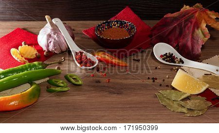 Spices and seasonings. A mixture of peppers, garlic, ginger and lemon on a wooden table. Still Life