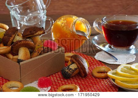 Tea with homemade cookies, orange jam, bagels and lemon. Homemade cookies and bagels in the box, orange jam in a glass jar. Slices of lemon and tea in a transparent cup