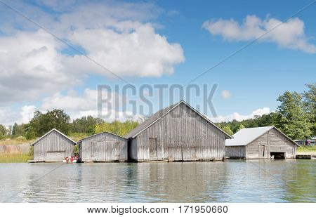 Gray old boathouses blue sky and white clouds in the archipelago in Aaland Finland