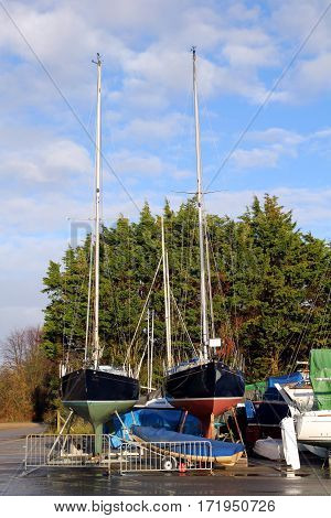 Two sailing boats on stands in a boatyard with trees and blue sky in background