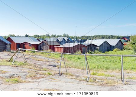 Many red and gray boathouses in the old fishing harbor in the archipelago in Aaland Finland