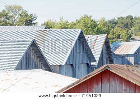 Roofs of corrugated iron on gray and red decayed boathouses in the archipelago in Aaland Finland
