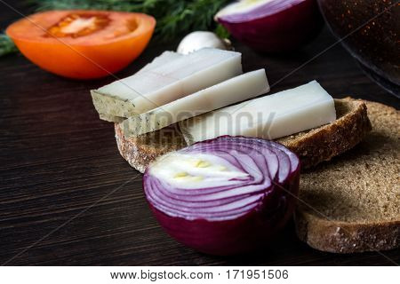 Ukrainian traditional food is lard (salo) with bread with red onions on the background of the tomato with garlic on wooden table. Small depth of focus