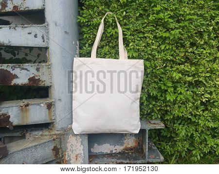 A canvas tote bag hanging on a leaf wall.