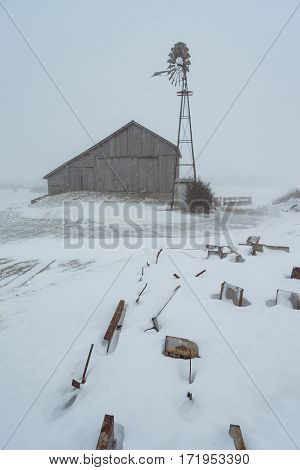 An old barn and windmill in a snowy midwest landscape - near Avilla, Indiana, United States of America. - Winter Farming